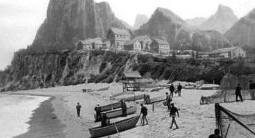 The village above the beach scene exists only as a matte painting.  Easier and quicker to do when shooting in black and white.